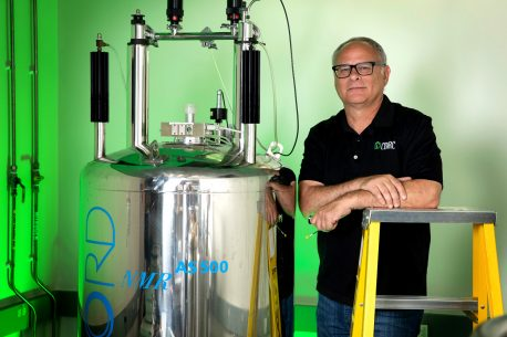 Salk Professor Joseph Noel, pictured in his lab, next to an NMR spectroscopy machine, which is used to decipher the detail of the electronic structures of molecules.